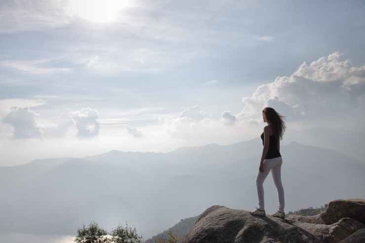 woman standing on a rock looking at nature s view